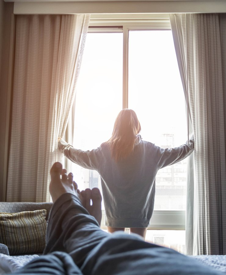 woman opening hotel room curtains