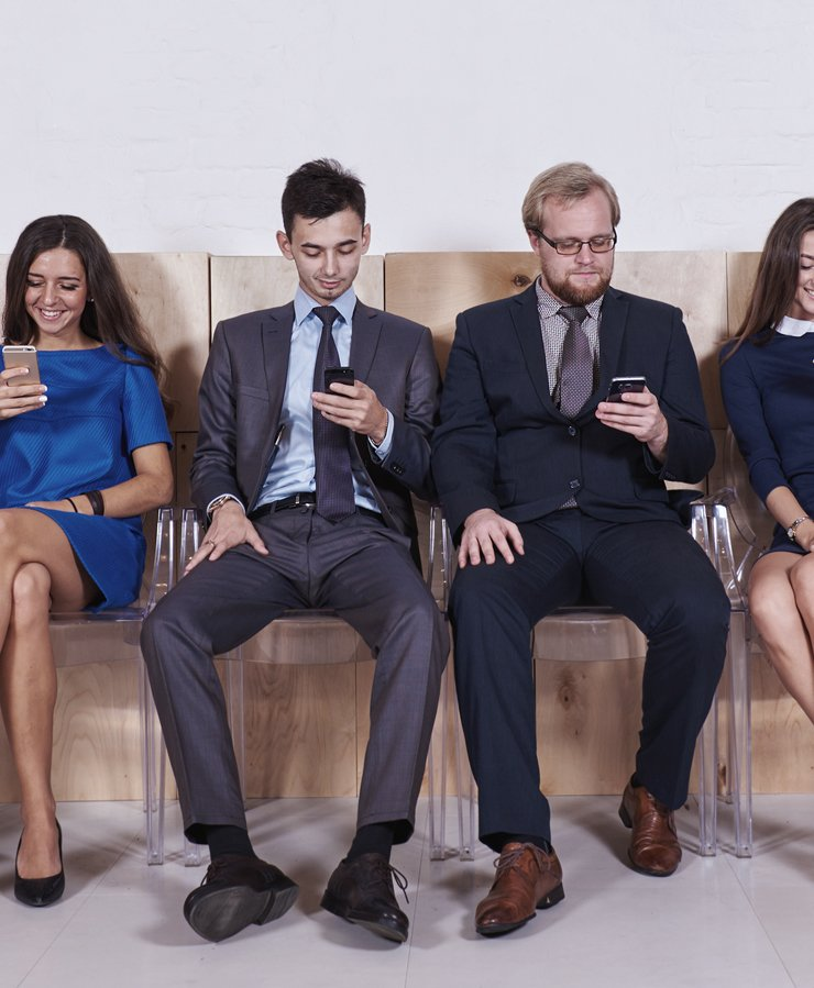 group of people sitting in a row looking at mobile phones