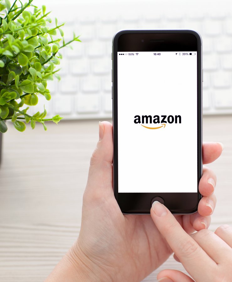 person holding phone with amazon logo
