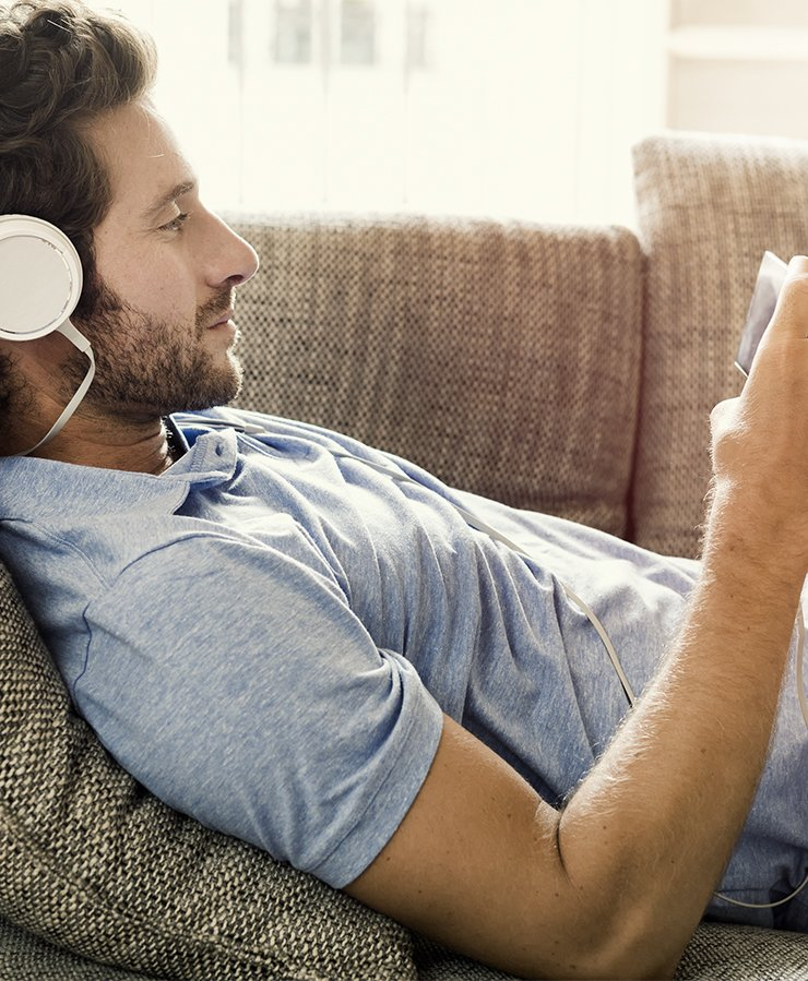 Man on couch watching video on his phone