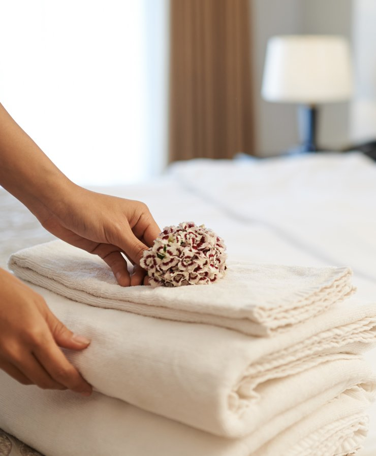 womans hands placing flower on bed linens in hotel