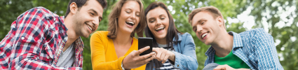 group of young people laughing and pointing at phone