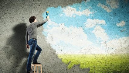 man painting a new mural over a plain wall