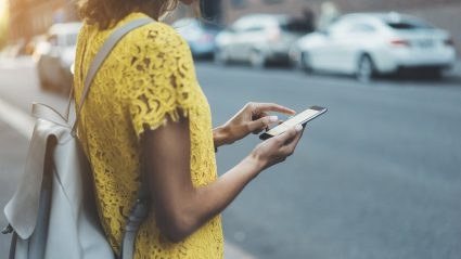 Woman looking at phone crossing street local search