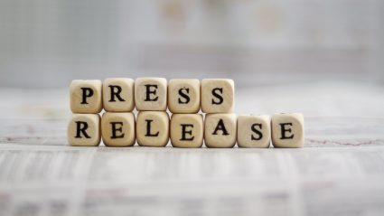 "Wood blacks stacked to spell ""Press Release"""
