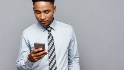 Business man standing looking at phone