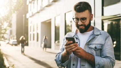 handsome man with classes on street smiling and looking at his phone