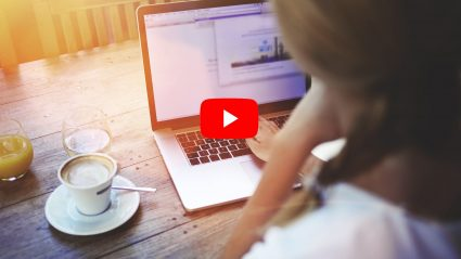 woman on computer looking at analytics youtube play button
