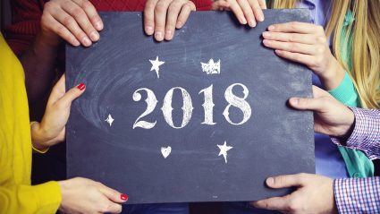 Hands holding chalkboard sign with 2018
