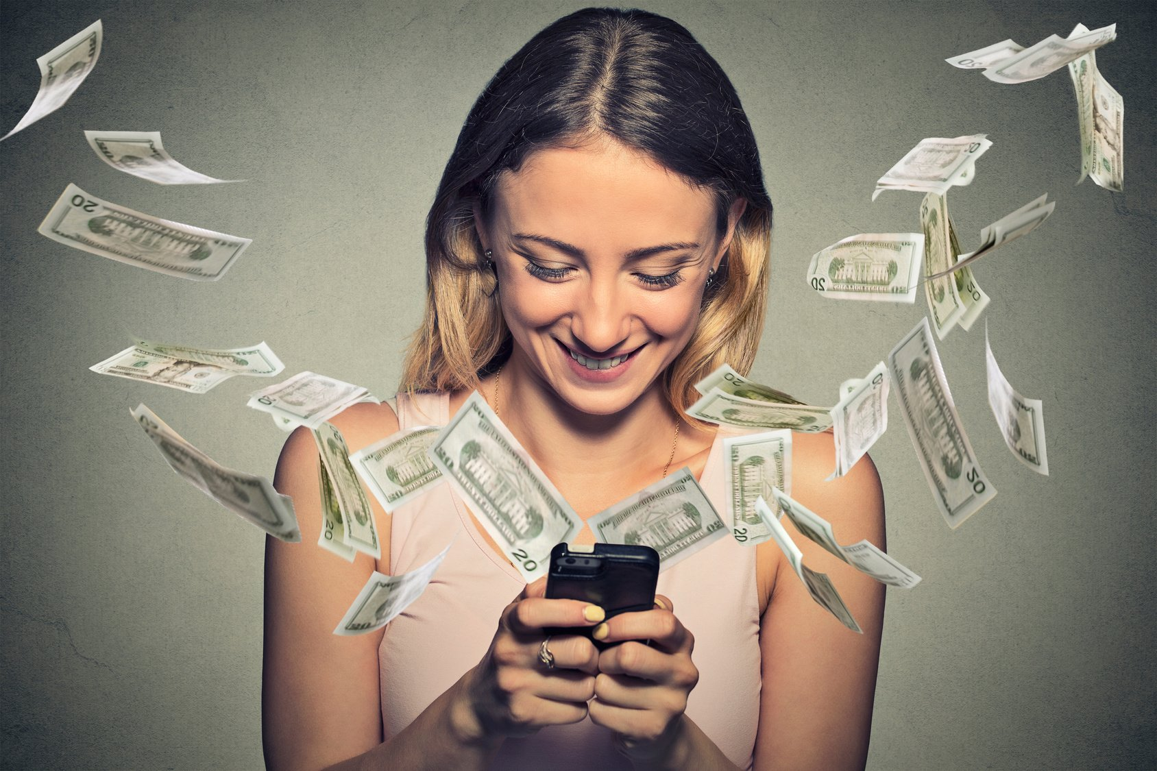 Money flying out of phone held by a smiling woman