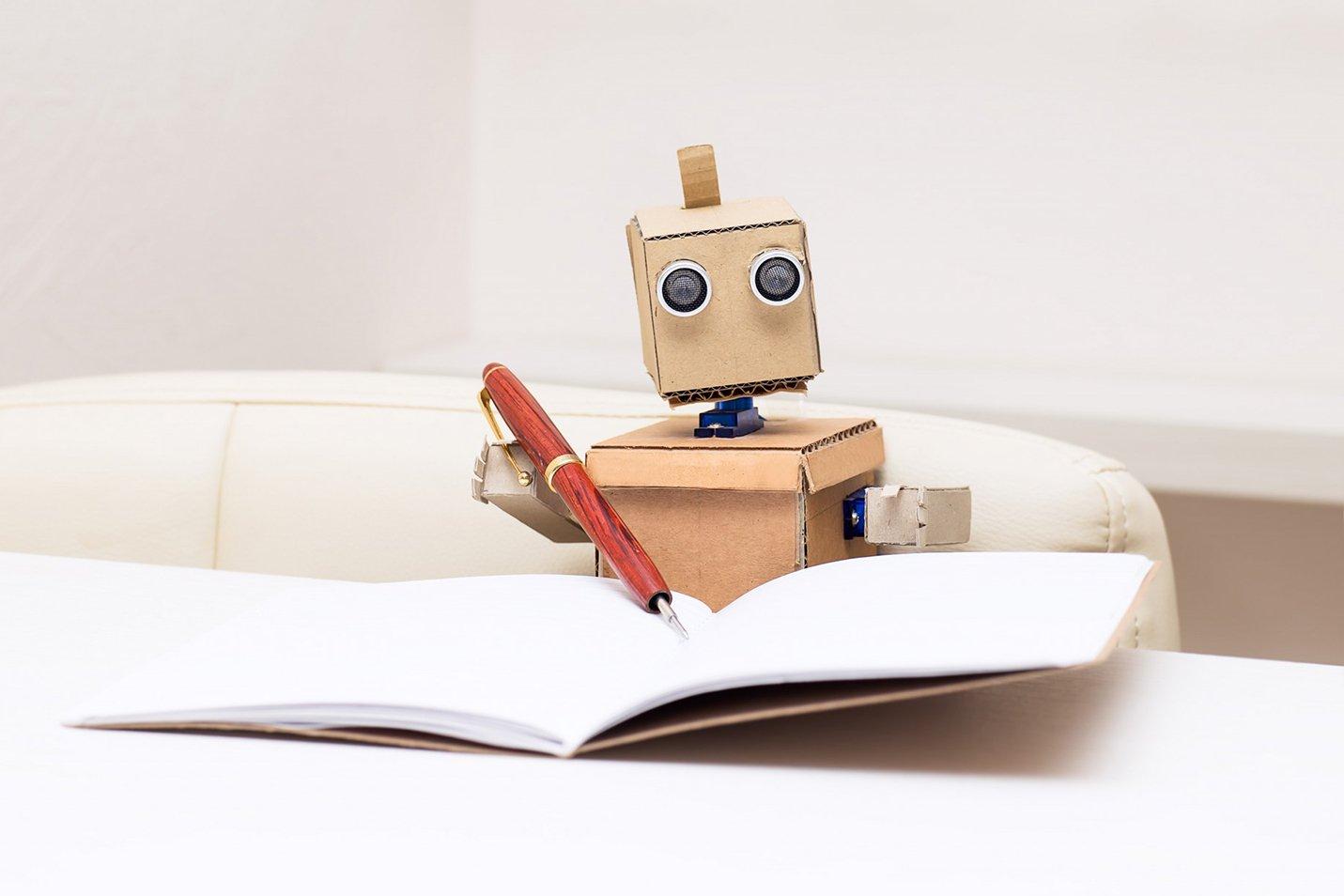 cardboard robot writing in notebook