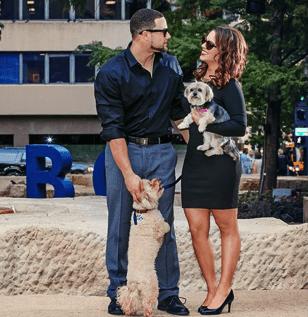 Couple standing next to Poodle/Bichon Frise