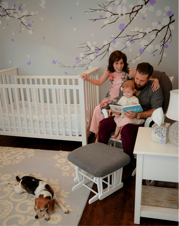 block and family reading to baby in nursery while bixby lays by feet