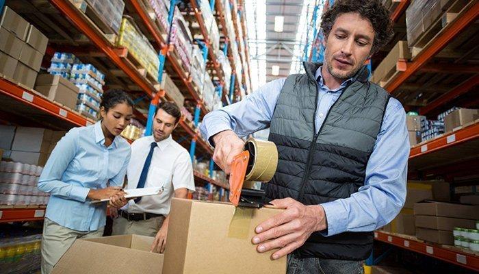 man taping cardboard box in warehouse