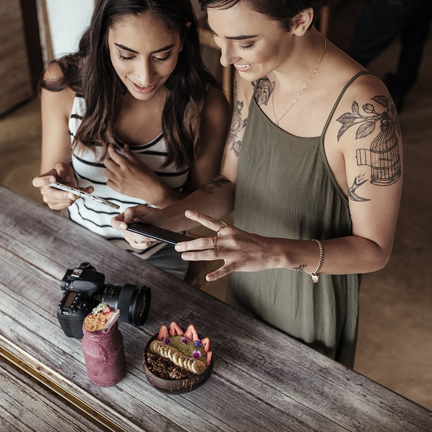 Two woman taking a photo of food