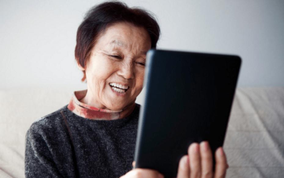 senior citizen woman smiling and looking at ipad