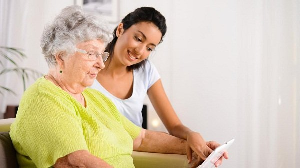 photo of young woman with grandma pointing to ipad