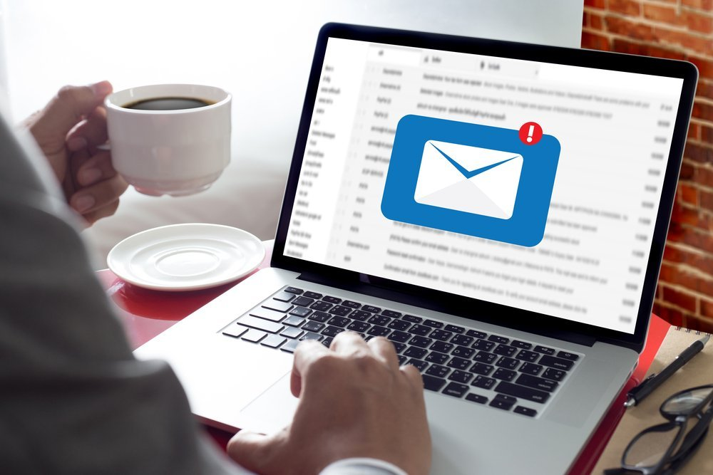 person drinking coffee with new email alert on laptop