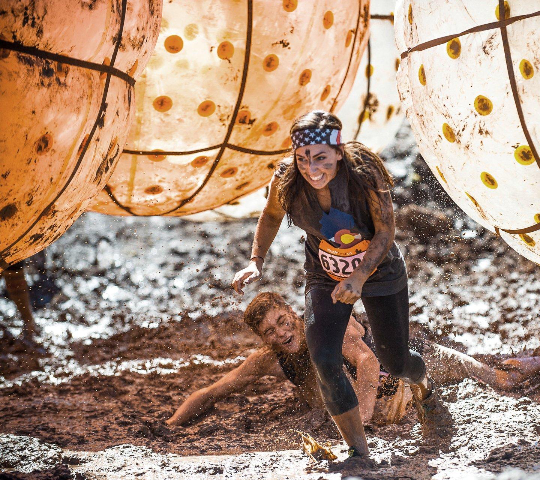 woman running through mud pit at muckfest
