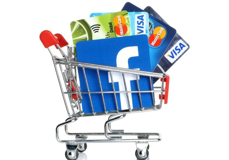shopping cart with credit cards and facebook logo inside