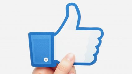 facebook like icon held by persons hand