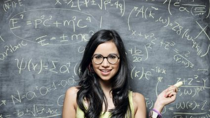 Girl standing in front of chalk board with mathematical equations