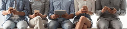 people sitting side by side holding mobile devices