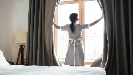Hotel service opening the drapes in a bedroom