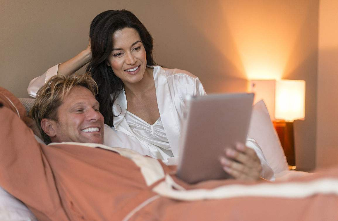Couple in hotel room looking at computer