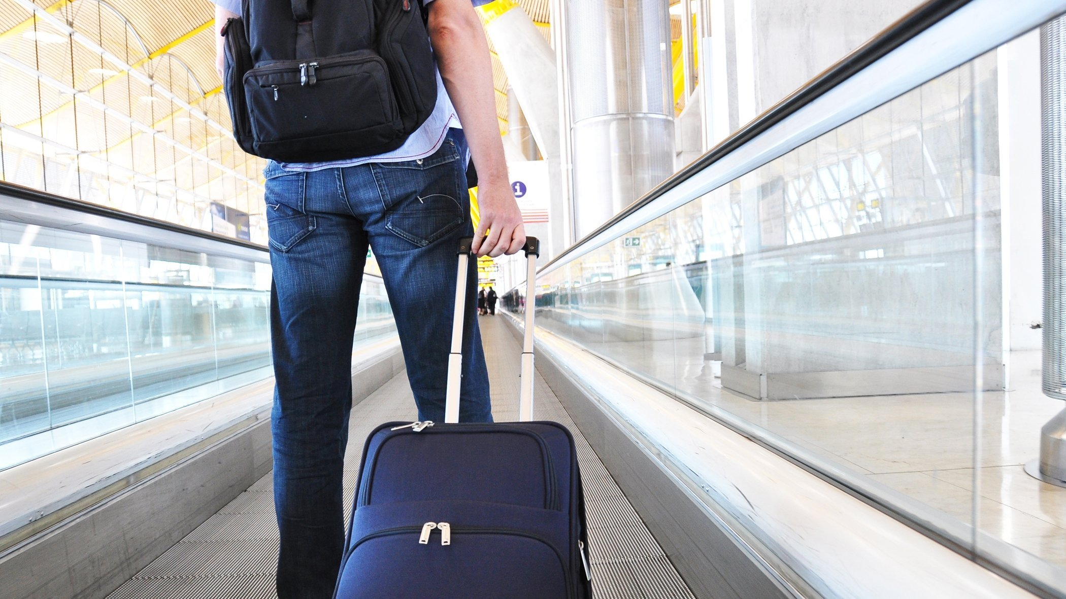 Man in airport wheeling luggage