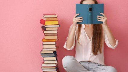 woman covering face with book on pink background