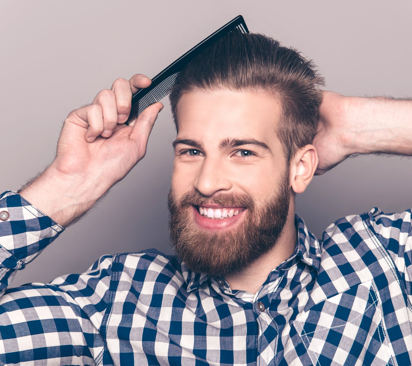 handsome man with beard combing hair