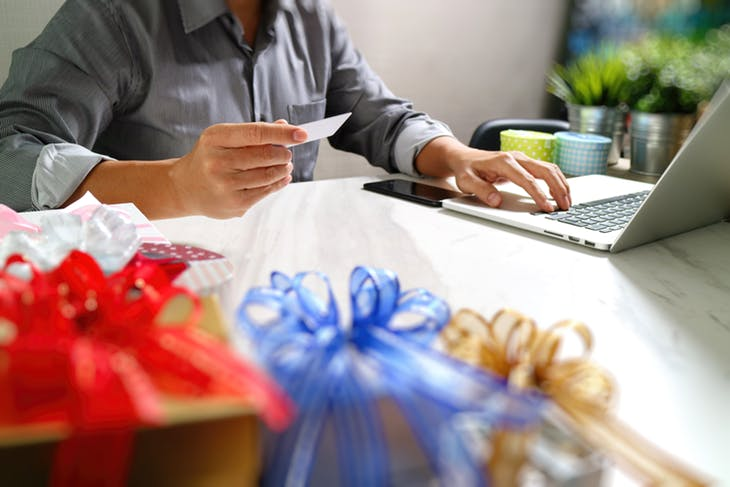 close up of man entering credit card at computer desk with gifts