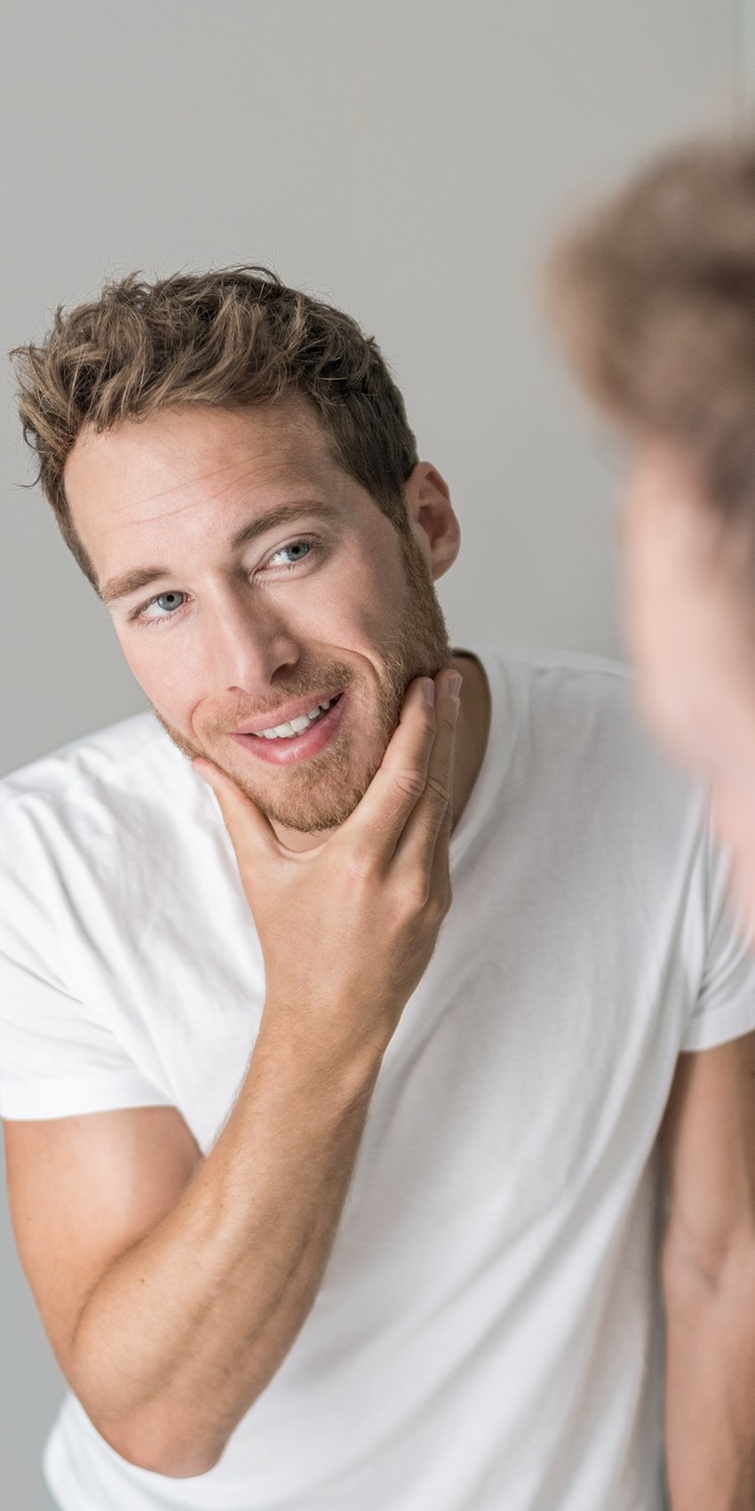 man looking at clear skin in mirror