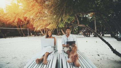 couple sitting on beach with laptops