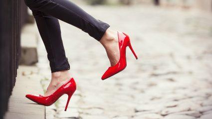 Woman walking on sidewalk with red high heels