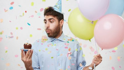 Man holding balloons and blowing out candle on birthday cupcake