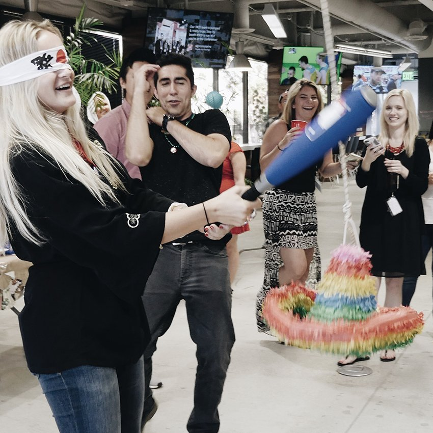 Wpromote team hitting a piñata