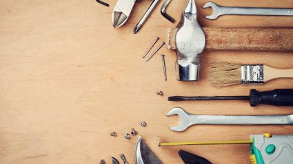 collection of tools laid out on wood surface