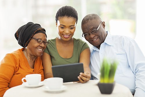 young woman with older parents all looking at ipad