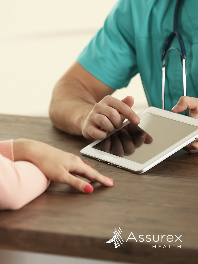 Doctor sitting with patient looking at tablet