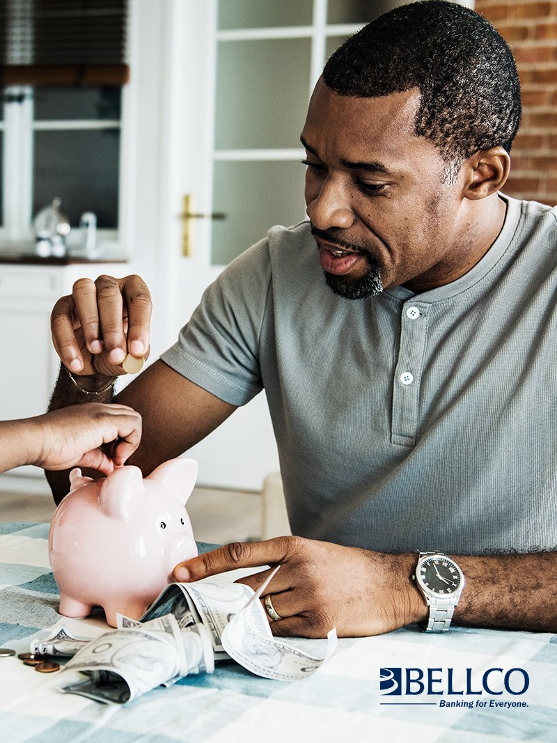 man putting coins into piggy bank