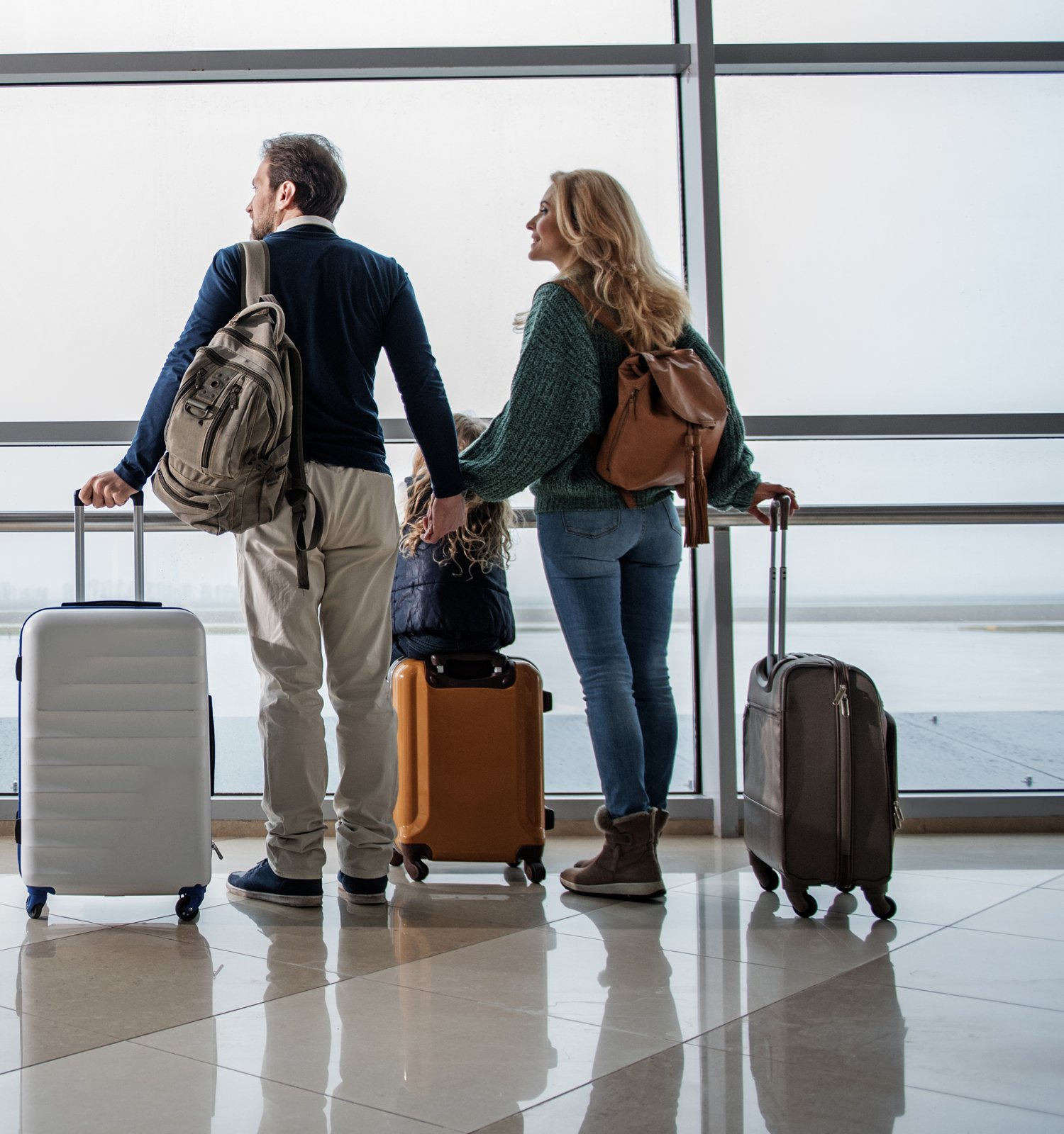 man and woman at airport with luggage looking out windows