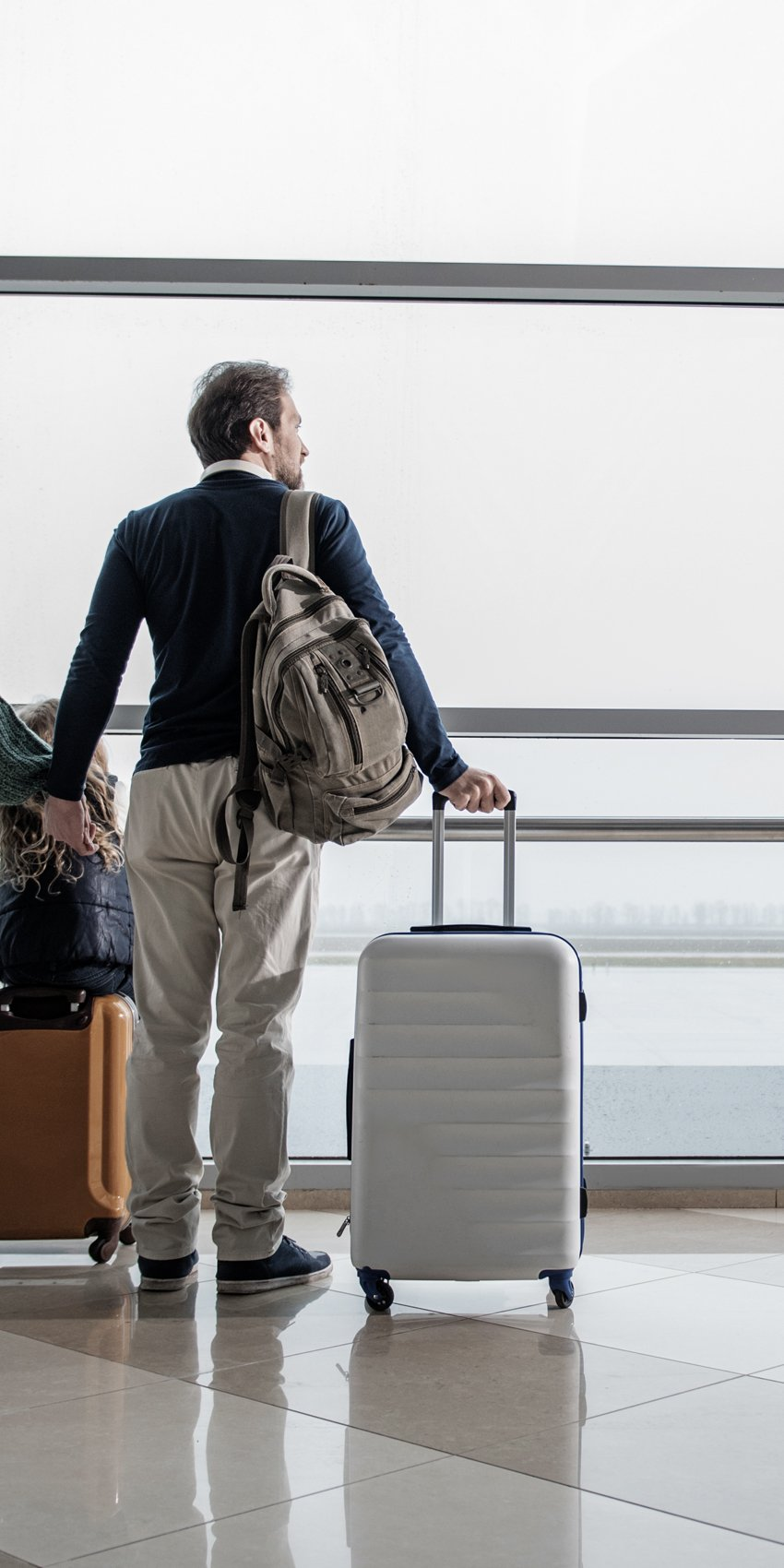 couple at airport with luggage looking out window