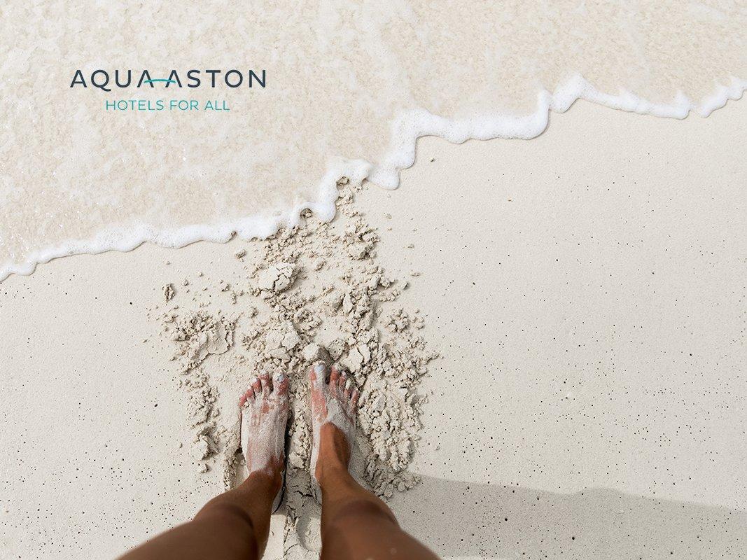 feet at shore of a white sandy beach