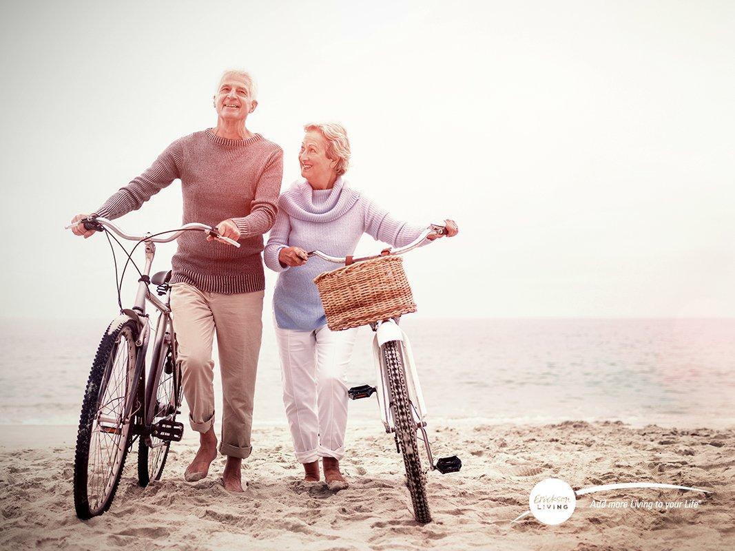 senior couple with bikes on beach