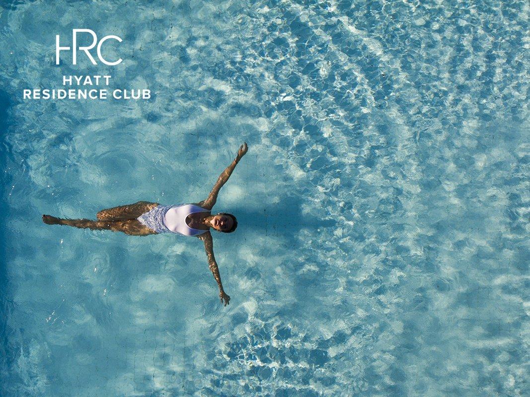 aerial shot of woman swimming in resort pool