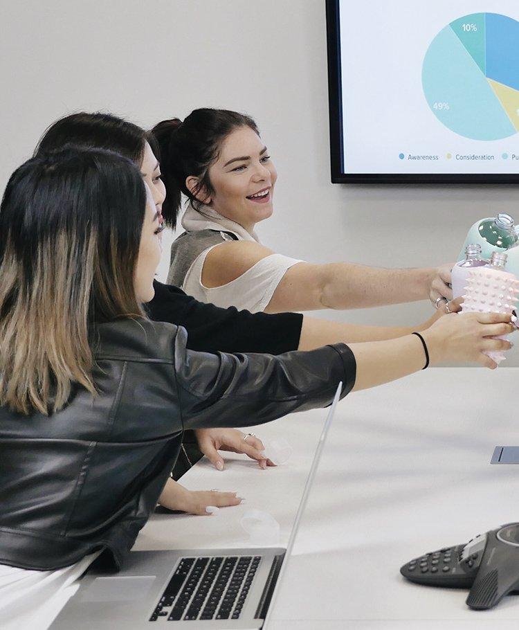 team meeting cheers with water bottles