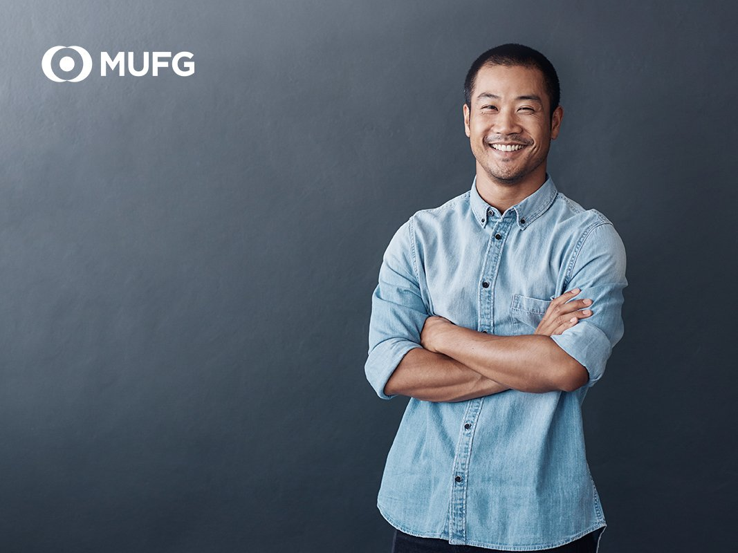 asian man smiling with folded arms dark grey background