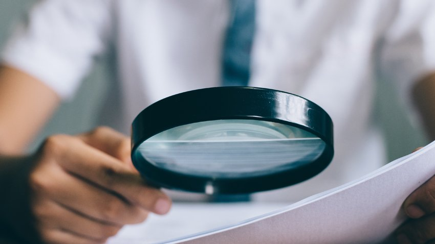 looking at paper with magnifying glass